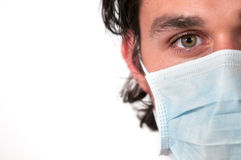 Man wearing medical mask. Headshot of a man wearing a blue medical mask on white background stock photos