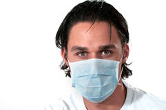 Man wearing medical mask. Headshot of a man wearing a blue medical mask on white background royalty free stock photo