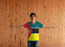 Man wearing Mozambique flag color shirt and standing with arms wide open on the wooden wall background stock photography