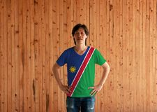 Man wearing Namibia flag color shirt and standing with akimbo on the wooden wall background. A white-edged red diagonal band and blue triangle, with a gold sun stock images