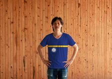 Man wearing Nauru flag color shirt and standing with akimbo on the wooden wall background royalty free stock images