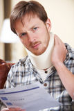 Man Wearing Neck Brace Reading Claim Letter Royalty Free Stock Photography