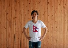 Man wearing Nepal flag on white shirt and standing with akimbo on the wooden wall background. Two red blue triangles: upper triangle is white moon and the stock image