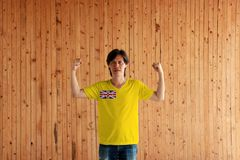 Man wearing Niue flag color of shirt and standing with raised both fist on the wooden wall background. Golden yellow flag with the Union Jack in the upper left stock photography