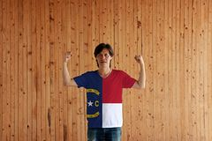 Man wearing North Carolina flag color of shirt and standing with raised both fist on the wooden wall background. The states of America royalty free stock image
