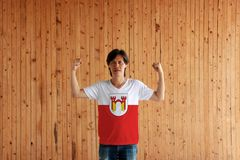 Man wearing Offenburg flag color of shirt and standing with raised both fist on the wooden wall background. It is in Baden-Wurttemberg, Germany royalty free stock image