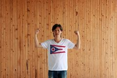 Man wearing Ohio flag color on white shirt and standing with raised both fist on the wooden wall background. The state of America royalty free stock images