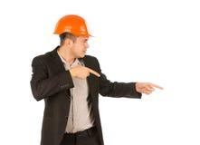 Man Wearing Orange Hard Hat Pointing to the Side Stock Image