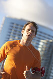 Man wearing orange t-shirt, jogging in city, listening to MP3 player strapped to arm, close-up (tilt) Royalty Free Stock Image
