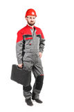 Man wearing overalls with red helmet with toolkit on white backg. Man wearing overalls with red helmet on white background Royalty Free Stock Image