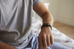 Man Wearing Pajamas Checking Smart Watch In Bedroom Stock Images