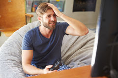 Man Wearing Pajamas Sitting In Chair And Playing Video Game Stock Images