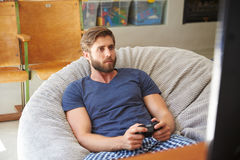 Man Wearing Pajamas Sitting In Chair And Playing Video Game Royalty Free Stock Photos