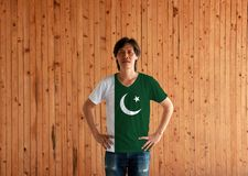 Man wearing Pakistan flag color shirt and standing with akimbo on the wooden wall background. A white star and crescent on a dark green field, with a vertical stock images