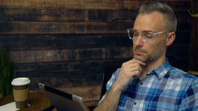 Man wearing plaid using tablet in cafe. Dolly shot of man wearing plaid using tablet in cafe stock video