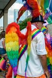 Man wearing Pride Parade Wings with LGBT Rainbow. Bristol, England - July 14, 2018: Man wearing Pride Parade Wings with LGBT Rainbow, shallow depth of field royalty free stock photo