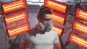 Man wearing protective mask and glasses holding polishing machine with red warm lights in background. stock video footage