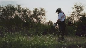 Man wearing protective mask and overalls working in garden stock video
