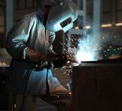 Man welding sheet matal using arc welding. Man in wearing protective suite arc welds sheet metal. Sparks fly around Royalty Free Stock Images