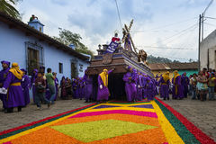 Man wearing purple robes, carrying a float anda during the Easter celebrations, in the Holy Week, in Antigua, Guatemala. Antigua, Guatemala - April 16, 2014 Stock Image