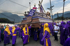Man wearing purple robes, carrying a float anda during the Easter celebrations, in the Holy Week, in Antigua, Guatemala. Stock Images