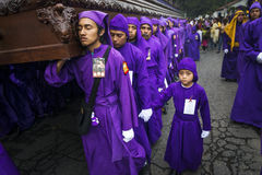 Man wearing purple robes, carrying a float anda during the Easter celebrations, in the Holy Week, in Antigua, Guatemala. Stock Photos