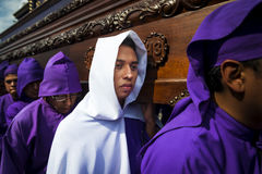 Man wearing purple and white robes, carrying a float anda during the Easter celebrations, in the Holy Week, in Antigua, Guatemal Royalty Free Stock Photos