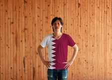 Man wearing Qatar flag color shirt and standing with akimbo on the wooden wall background. A white band on the hoist side, separated from a maroon area on the stock image