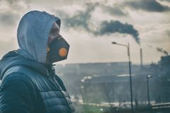 Man wearing a real anti-pollution, anti-smog and viruses face mask royalty free stock image
