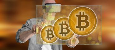 Man wearing a reality virtual headset touching a bitcoin currency concept on a touch screen. With his fingers Royalty Free Stock Photo