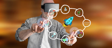 Man wearing a reality virtual headset touching a business strategy concept on a touch screen Stock Image