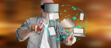 Man wearing a reality virtual headset touching a cloud computing concept on a touch screen. With his fingers Stock Photos