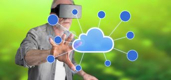Man wearing a reality virtual headset touching a cloud networking on a touch screen. With his finger Royalty Free Stock Photo
