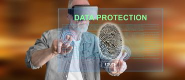 Man wearing a reality virtual headset touching a data protection concept on a touch screen Stock Image
