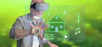 Man wearing a reality virtual headset touching a digital smart home automation concept on a touch screen Royalty Free Stock Images