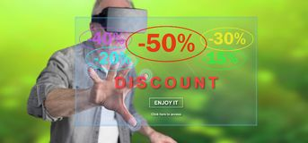 Man wearing a reality virtual headset touching a discount concept on a touch screen. With his finger Royalty Free Stock Photography