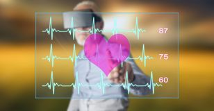Man wearing a reality virtual headset touching a heart beats graph concept on a touch screen. With his finger Stock Photography