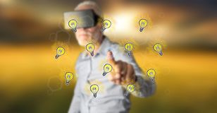 Man wearing a reality virtual headset touching light bulbs on a touch screen. With his finger Royalty Free Stock Photo