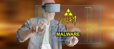 Man wearing a reality virtual headset touching a malware concept on a touch screen Royalty Free Stock Photo