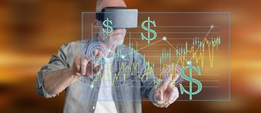 Man wearing a reality virtual headset touching a stock exchange concept on a touch screen Royalty Free Stock Photo