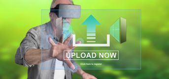 Man wearing a reality virtual headset touching an upload concept on a touch screen Stock Image