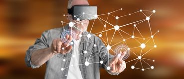Man wearing a reality virtual headset touching a virtual network concept on a touch screen Royalty Free Stock Photography