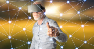 Man wearing a reality virtual headset touching a virtual network on a touch screen Royalty Free Stock Images