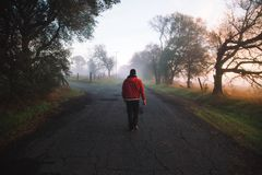 Man Wearing Red Hooded Jacket Standing on Road Stock Photos