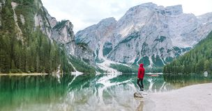 Man Wearing Red Hoodie Standing Near Body of Water With View of Mountains Stock Photos