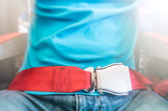 Man wearing red seat belt. Safety measures. Partial view of man in blue t-shirt and jeans wearing red seat belt. Safety measures on board. Precautions on plane stock photos