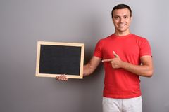 Man wearing red shirt against gray background. Studio shot of man wearing red shirt against gray background Stock Photo