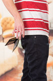 Man wearing red white striped shirt and dark jeans. Dropping wallet Stock Photo