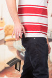 Man wearing red white striped shirt and dark jeans. Dropping wallet Royalty Free Stock Photos