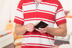 Man wearing red white striped shirt holding wallet Stock Images